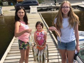 Young Girls Holding Stringer Of Fish On Dock